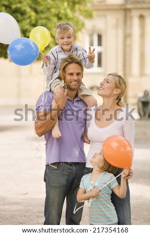 Young man carrying his son on his shoulders and his wife and daughter looking at him - stock photo