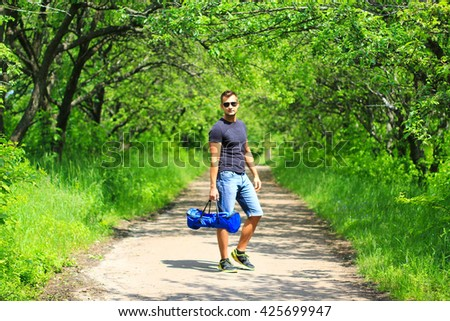 young man carrying hoverboard in a bag outdoors in the park - his personal portable eco transport, gyroboard, hyroboard, smar balance wheel, electrical scooter