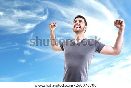 Young man celebrating on beautiful day - stock photo