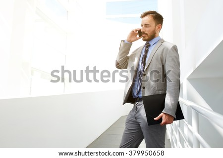 Young man CEO talking on mobile phone with partner about signing a contract with investors, male skilled financier holding folder with documents while calling with cell telephone to his colleague - stock photo