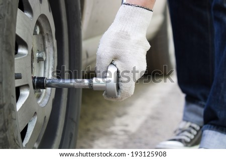 Young man changing wheel - stock photo