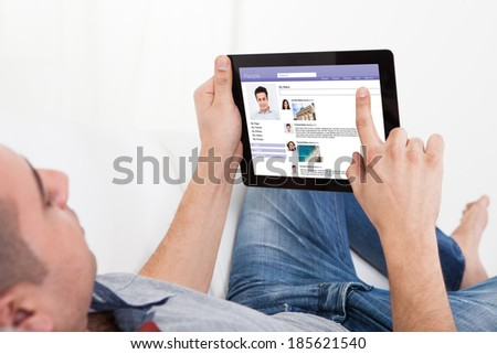 Young man chatting on digital tablet while lying on sofa at home - stock photo