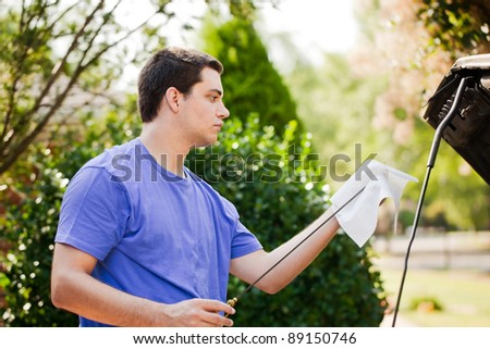 Young man checking his oil - stock photo