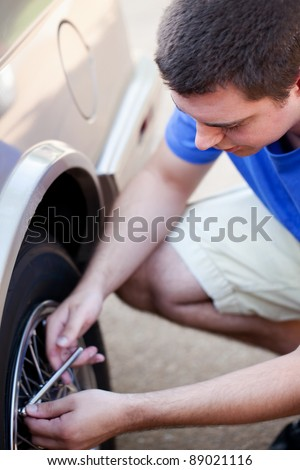 Young man checking tire pressure with tire gauge - stock photo