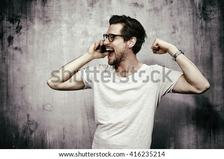 Young man cheering on cell phone, studio - stock photo