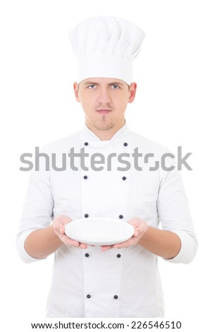 young man chef  in uniform showing empty plate isolated on white background - stock photo