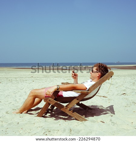 Young man chilling on the beach  - stock photo