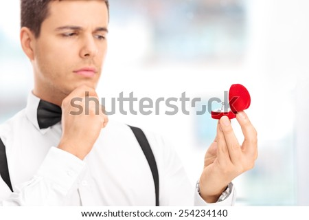 Young man choosing an engagement ring in a jewelry store  - stock photo