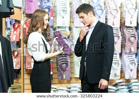 Young man choosing shirt and necktie during apparel shopping at clothing store - stock photo
