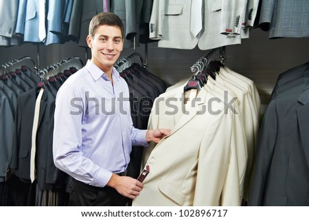 Young man choosing suit jacket during apparel shopping at clothing store