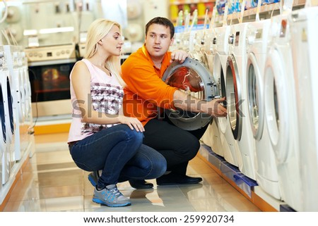 Young man choosing washing machine in home appliance shopping mall supermarket - stock photo