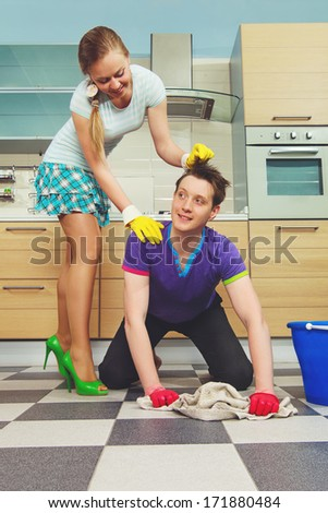 Young man cleaning floor and looking at his girlfriend