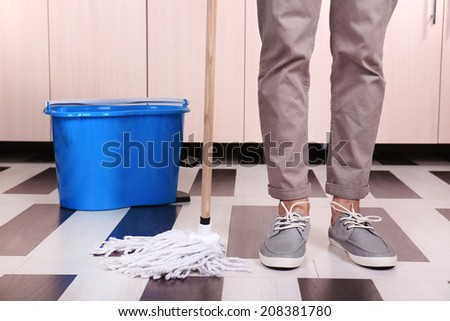 Young man cleaning floor in room - stock photo