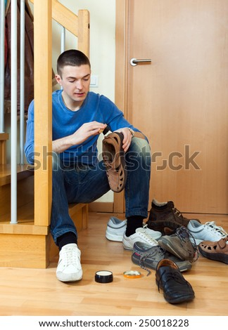 Young  man  cleaning footwear sitting on the steps at home