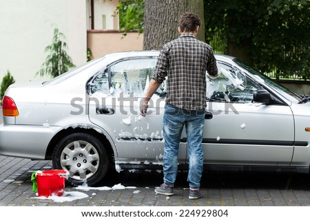 Young man cleaning his car on the backyard - stock photo