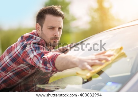 Young man cleaning his car outdoors.He is polishing rear windshield. - stock photo