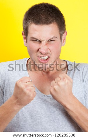 Young man clenching is fist in anger - stock photo