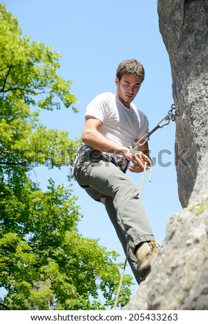 young man climbing a rock wall in the French Alps