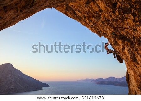 Young man climbing in cave at sunset