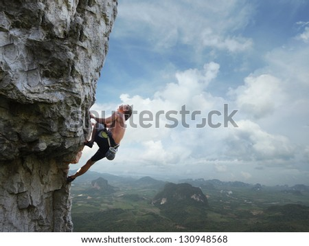 Young man climbing natural rocky wall with tropical valley on the background - stock photo
