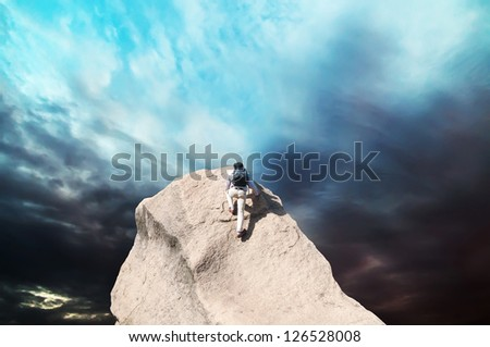 Young man climbing on a limestone wall with blue sky on the background