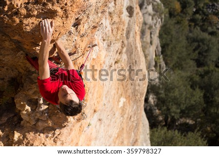 Young man climbing on a limestone wall with wide valley on the background.