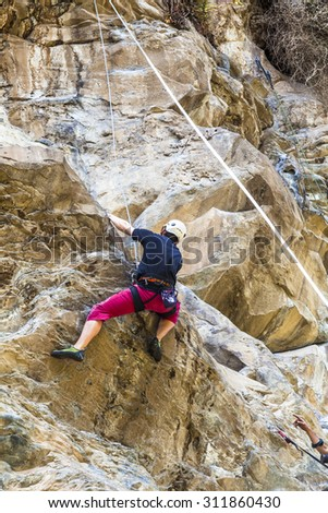 Young man climbing on a rock wall - stock photo