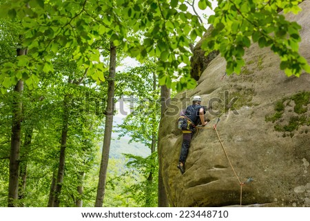 Young man climbing on a stone in the forest - stock photo