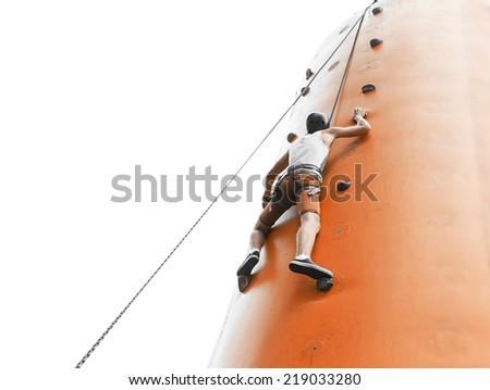 Young man climbing on an artificial wall - stock photo