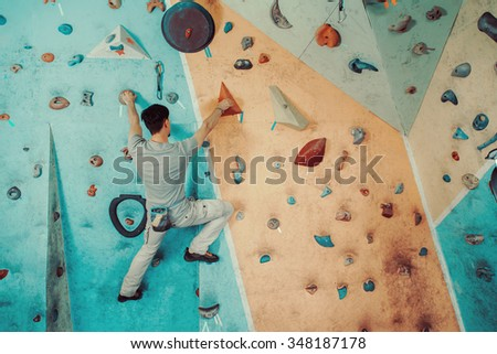 Young man climbing on artificial boulders wall indoor, rear view - stock photo
