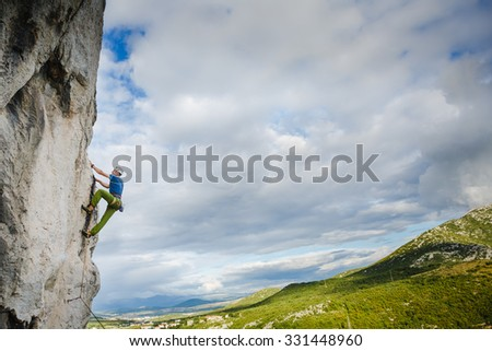 Young man climbing on rocky wall with sky background