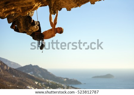 Young man climbing on roof in cave, view of coast below