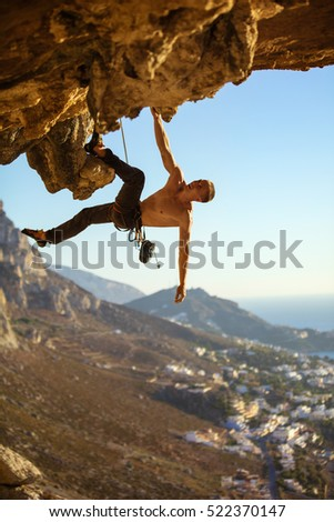 Young man climbing on roof of cave against view of coast below