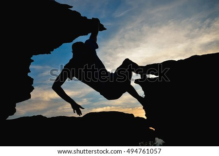 Young man climbing on top of rock mountain