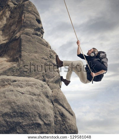 young man climbing the mountain - stock photo