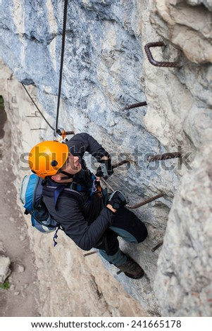 Young man climbing vertical wall on via ferrata - stock photo