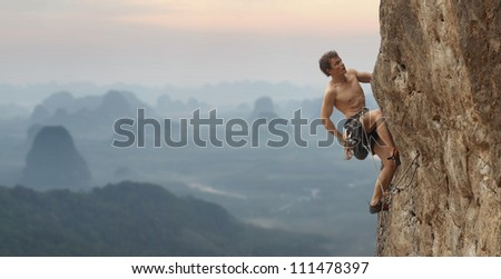 Young man climbing vertical wall with blurred valley view on the background
