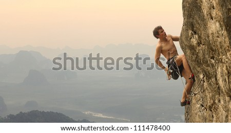 Young man climbing vertical wall with valley view on the background