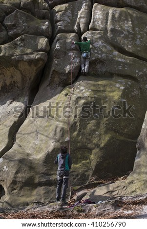 Young man climbs on a cliff with a rope. - stock photo