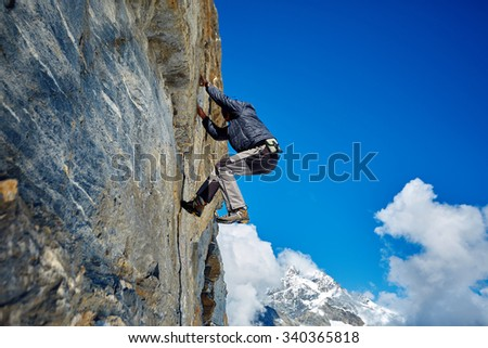 Young man climbs on a rocky wall, against a blue sky