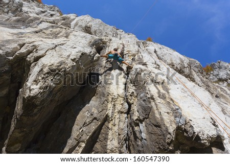 Young man climbs the rock wall to the peak