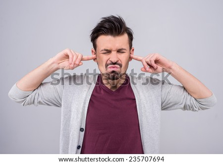 Young man close his ears because too loud, isolated on a gray background. - stock photo