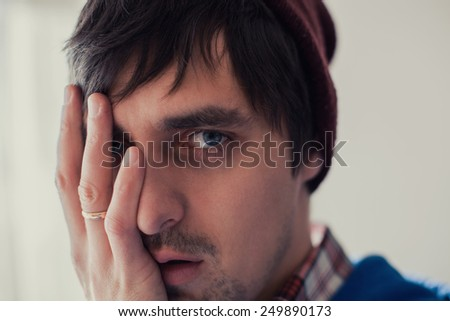 young man closes his eye with his hand