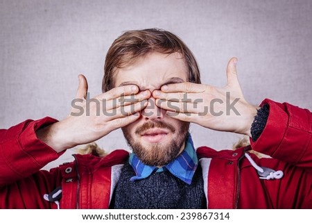 young man closes his eyes with his hands - stock photo