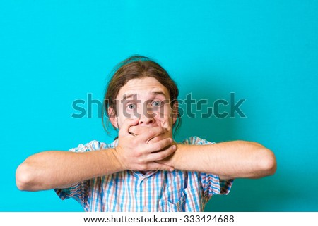 young man closes the mouth with her hands - stock photo