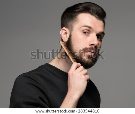 young man comb his beard and moustache on gray background - stock photo