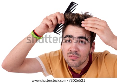 young man combing his hair with a comb, isolated on white, studio shot - stock photo