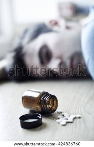 Young Man Committing Suicide By Overdosing On Medication - stock photo