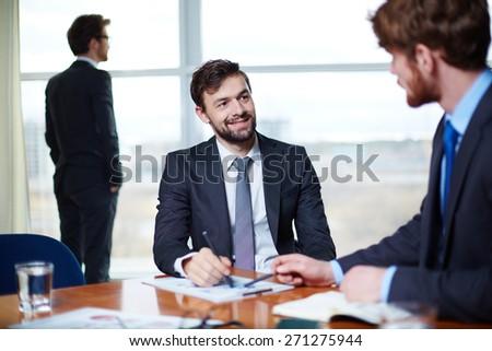 Young man communicating with his colleague in office - stock photo