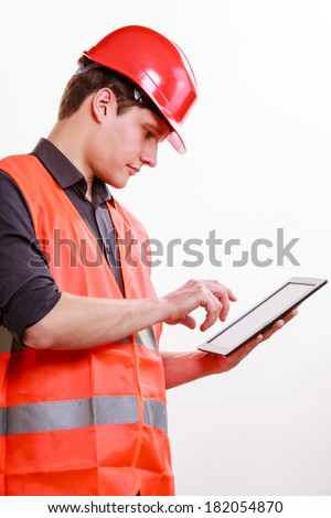 Young man construction worker builder in orange safety vest and red hard hat using tablet touchpad isolated on white. Technology in industrial work. Studio shot. - stock photo